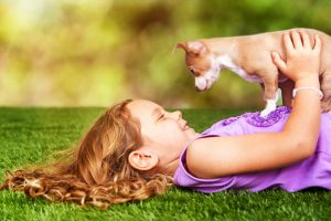 Cute little girl laying on grass outdoors with puppy on her chest looking down at her